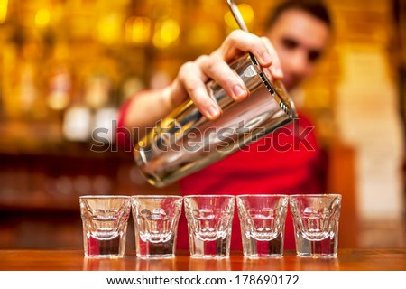 Bartender pours alcoholic drink into small glasses  - stock photo