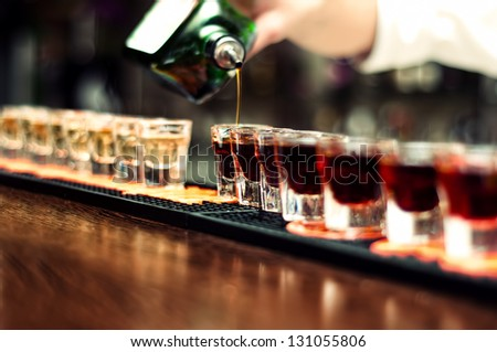 Bartender pours alcoholic drink into small glasses on bar - stock photo