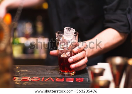 Bartender preparing a cocktail. Glass on the bar - stock photo