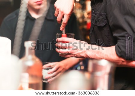 Bartender preparing a cocktail. Process of preparation - stock photo