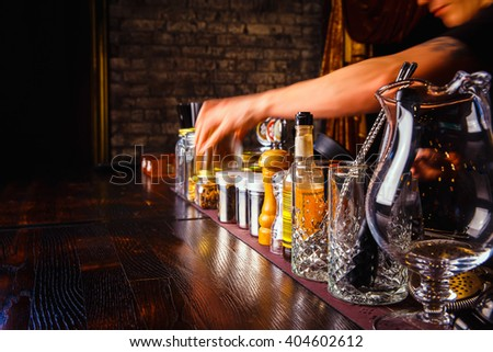 Bartender works with tools on bar at the night club