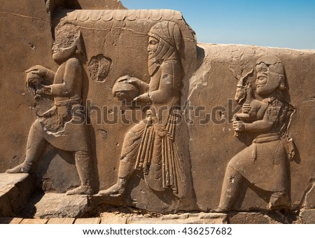 Bas relief carvings of dignitaries and representatives bringing gifts to the Achaemenian King in Persepolis of Shiraz. - stock photo