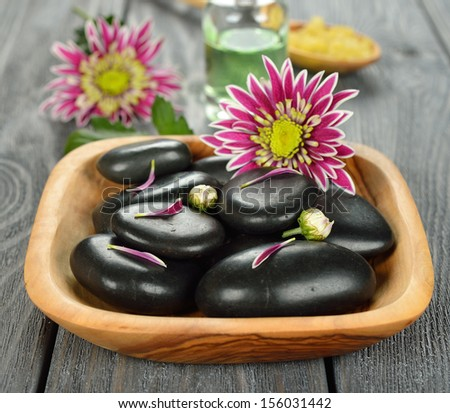 Basalt stones to massage and stone therapy, in a wooden bowl on a gray background