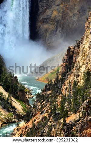 Base of Yellowstone's famous Lower Falls is covered in a rush of water and flying mist.  Canyon walls are steep and rugged. - stock photo