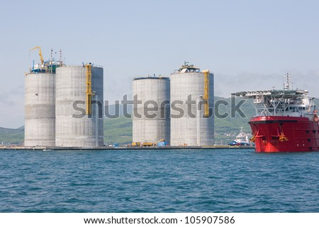 Base oil drilling platform and ocean-going tug. Sea of Japan. Russian coast. - stock photo