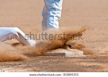 Base runner sliding into third base, close up on base