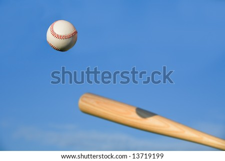 Baseball about to be struck by baseball bat with blue sky background. - stock photo