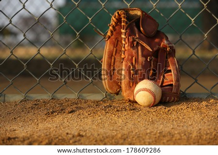 Baseball and Glove against the Field Fence - stock photo