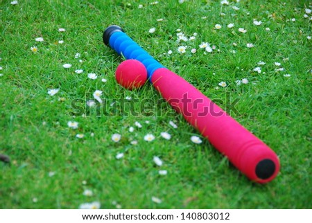 Baseball ball and bat on green grass - stock photo