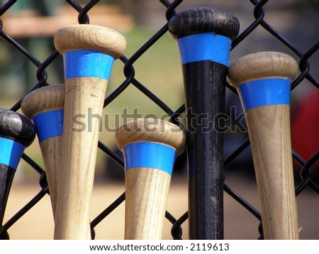 Baseball bats leaning against a batting cage fence. - stock photo
