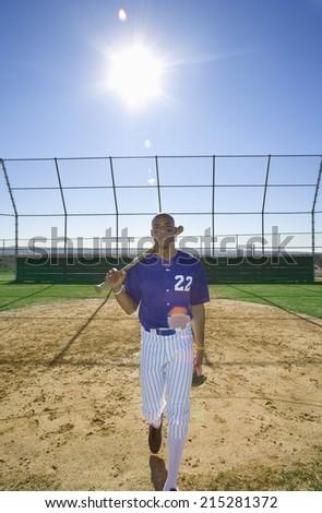 Baseball batter, wearing number �¢â�¬��22�¢â�¬â�¢ blue uniform, walking on pitch with bat resting on shoulder, front view, portrait (lens flare) - stock photo