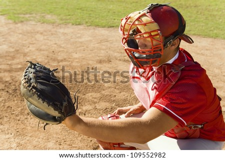Baseball catcher ready to catch ball thrown by the pitcher - stock photo