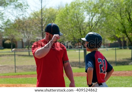 Baseball coach giving signals to teen player - stock photo