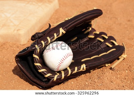 Baseball equipment on the field, with glove base and ball