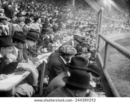 Baseball games were reported via telegraph operators and the action and changing scores were posted to large public scoreboards. Polo Grounds, New York City, October 9, 1913. - stock photo