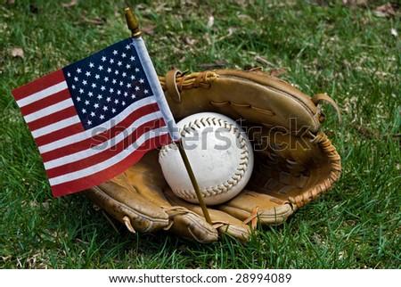 Baseball, glove and flag on green grass - stock photo