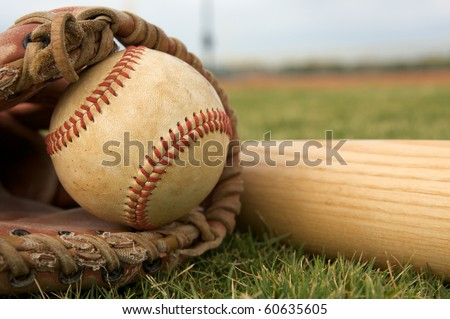 Baseball in a Glove on the field with the bat