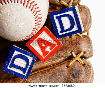 baseball in an old baseball glove with the word Dad written in colorful wooden blocks, isolated on white - for father's day concept - stock photo