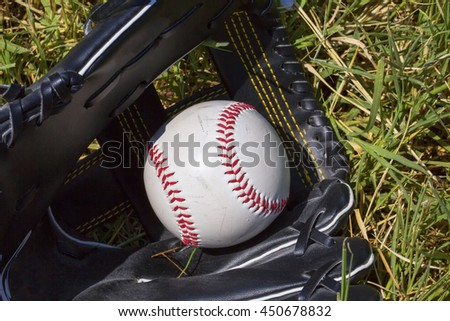 Baseball in glove over grass, horizontal image - stock photo