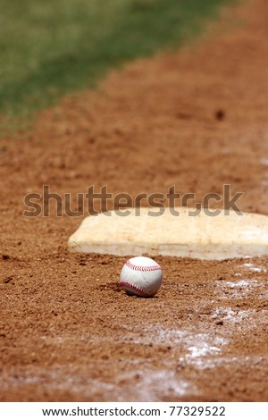 baseball in the dirt at thirdbase - stock photo