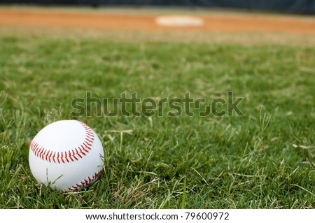 Baseball on field with base and outfield in background.