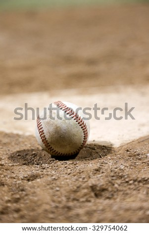 Baseball on top of homeplate with dirt and pitcher's mound in background