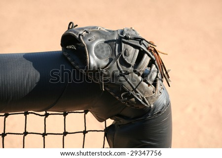 Baseball or softball glove resting on a dugout fence - stock photo