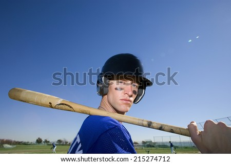 Baseball player, in blue uniform, helmet and face paint, standing on pitch with bat resting on shoulder, side view, close-up, portrait - stock photo