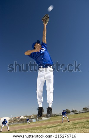 Baseball player, in blue uniform, jumping up to catch ball in protective glove during competitive game (surface level, tilt) - stock photo