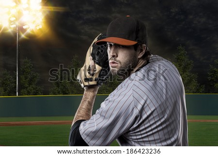 Baseball Player on a Orange Uniform on baseball Stadium. - stock photo