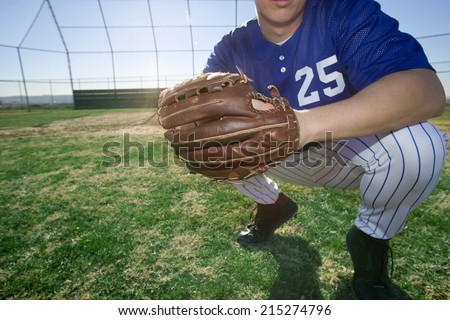 Baseball player, wearing number �¢â�¬��25�¢â�¬â�¢ blue uniform and glove, crouching on pitch, close-up, low section