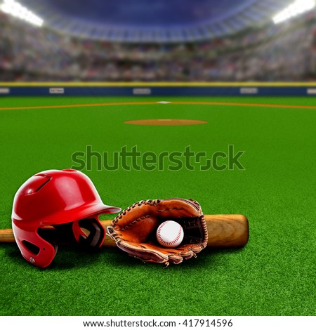 Baseball stadium full of fans in the stands with helmet, bat, glove and ball on the field. Deliberate focus on equipment and foreground with shallow depth of field on background. Copy space. - stock photo