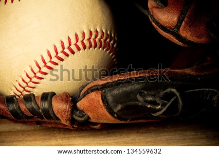 Baseball - This is a close up shot of an old baseball inside an old baseball glove on a wood background. Shot in a warm retro color tone. - stock photo