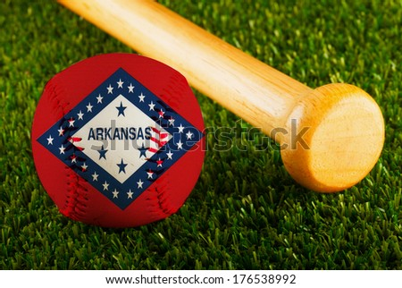 Baseball with Arkansas flag and bat over a background of green grass - stock photo
