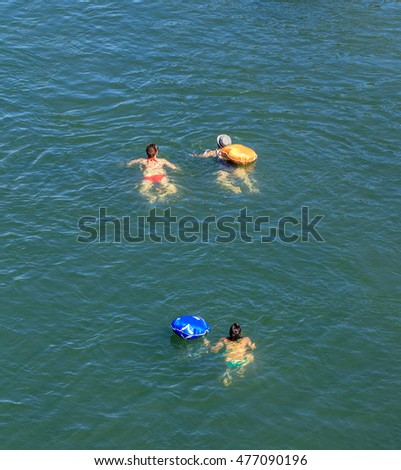 Basel, Switzerland - 27 August, 2016: people swimming in the Rhine river, view from the Johanniterbruecke bridge. Basel is a city on the Rhine river in northwestern Switzerland.