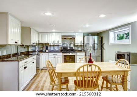 Basement kitchen room with rustic dining table set in Mother-in-law apartment - stock photo