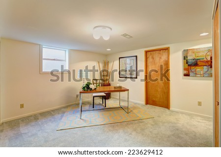 Basement light tone office room with desk and chair in the corner - stock photo