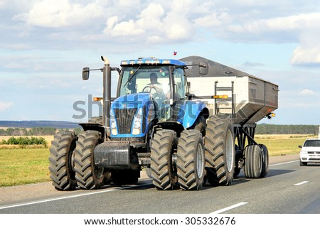BASHKORTOSTAN, RUSSIA - AUGUST 27, 2011: Blue modern agricultural tractor New Holland at the interurban road. - stock photo