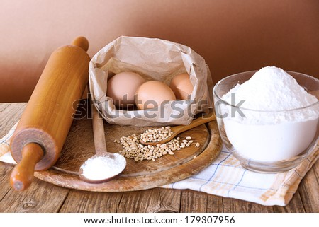 Basic baking ingredients on kitchen table, over brown background.