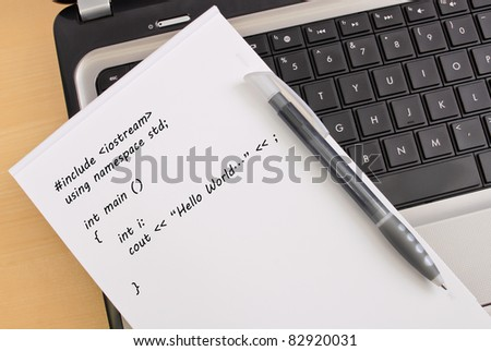 Basic Programming on Note Pad next to Computer - stock photo