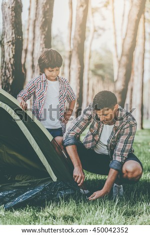 Basics of camping. Cheerful father and son pitching a tent while camping in the forest together - stock photo