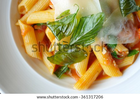 basil and cheese on top of penne pasta