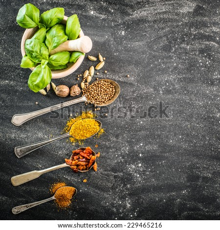 basil in a wooden mortar and spices spoons on a black background - stock photo