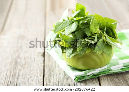 Basil leaves in bowl grey wooden background - stock photo
