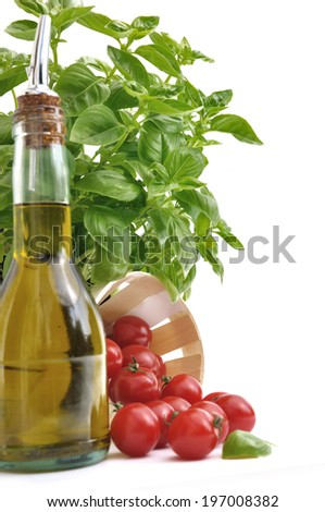 basil leaves on top of cherry tomatoes and olive oil bottle on white background
