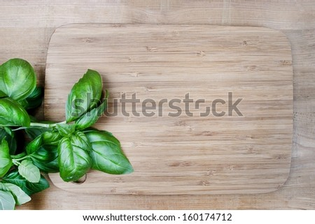 Basil leaves on wooden background. Copy space - stock photo