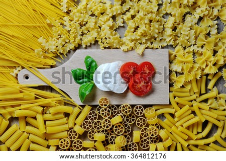 basil, mozzarella and tomato on chopping board, and italian pasta various types and shapes - stock photo