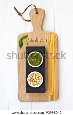 Basil pesto and pinenuts on a wooden board - stock photo