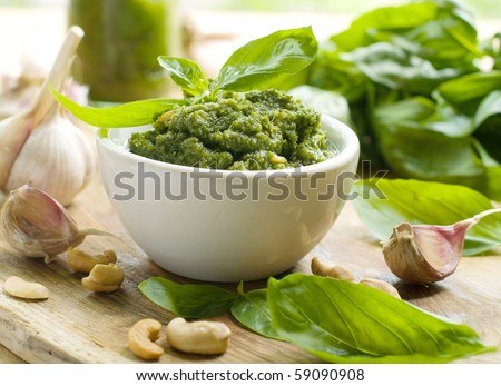 Basil pesto in a small bowl, with fresh basil leaves - stock photo