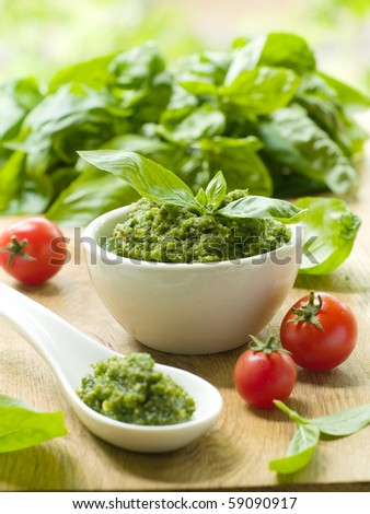 Basil pesto in a small bowl, with fresh basil leaves. - stock photo
